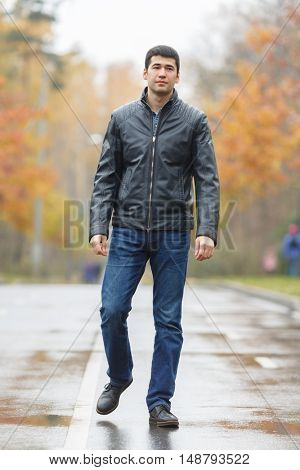 Full length portrait of young dark-haired man in black jacket on avenue in park, walking