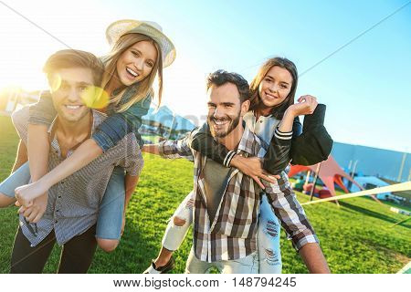 happy young men giving their girlfriends piggyback rides in the park