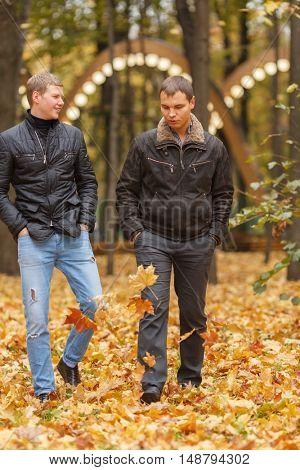 two young man in black jacket in autumn park walking on yellow leaves, one of them smiling