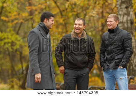 three friends dressed in warm clothes standing in alley in park and laughing