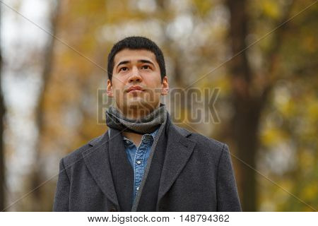 half length portrait of young dark-haired man in black jacket in alley in park, close-up