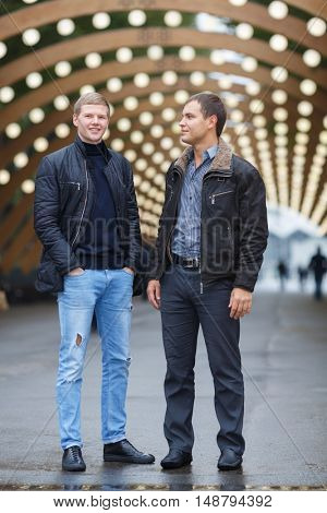 two young handsome man in black jacket posing on background of lights installation main park alley
