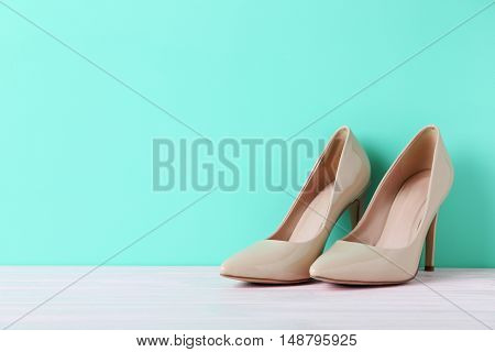 Pair Of Beige Women's High-heeled Shoes On Wooden Table