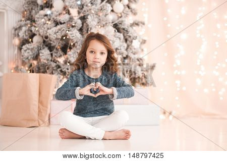 Cute baby girl 4-5 year old showing heart with hands sitting over christmas tree with presents. Holiday shopping.