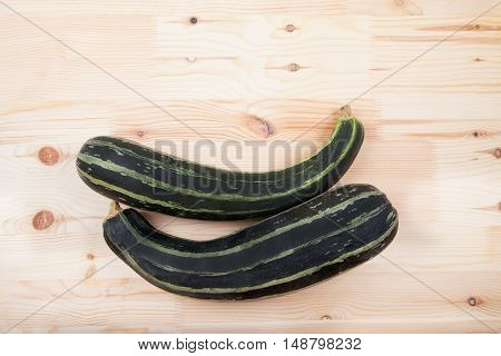 Green Zucchini Squash Lie On A Wooden Table