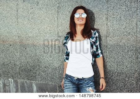 Hipster girl wearing white t-shirt and fashion sunglasses posing against wall, swag street style