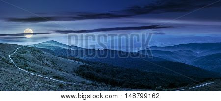 panoramic summer landscape with road through hillside meadow in mountains at night in full moon light