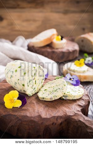 Herb butter with edible flowers on wooden cutting board, healthy food.