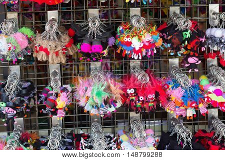 Bangkok Thailand - May 07 2016: The handmade colorful fabric doll-shape key chain hanging on the rack for sale in a souvenir shop at Chatuchak market.