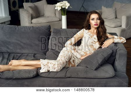 Gorgeous stunning woman in sexy white lace dress lying on gray couch and looking in camera. Vogue style fashion model portrait