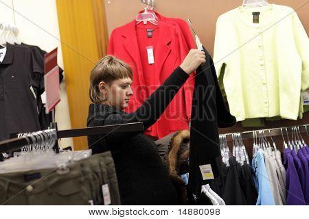 Woman Looks At Black Jacket