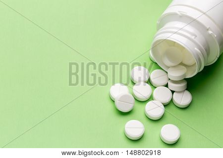 Heap of round white tablets and plastic pills bottle