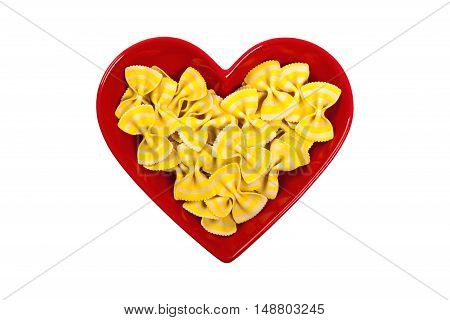 Lemon Flavored Fancy Bow Tie Pasta in Heart Shaped Bowl Isolated on white. Selective focus.