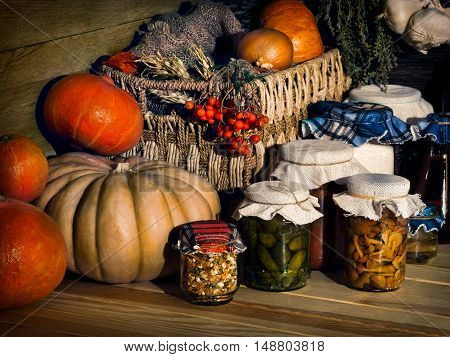 Retro still life with pumpkins and a glass jar with canned food - cucumbers mushrooms jam