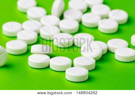 Heap of round white pills on green background
