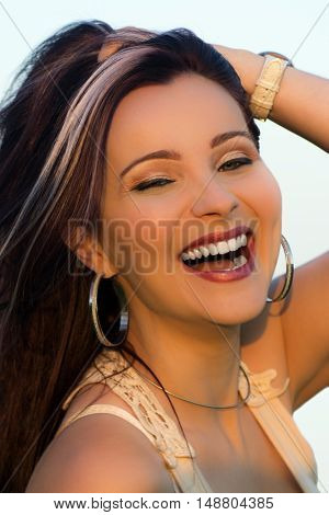 Beautiful happy laughing woman is posing outdoors.