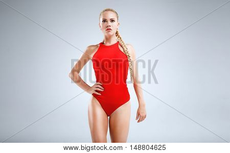 High fashion portrait of a slim and beautiful fitness model with blonde hair posing in a red bodysuit on a grey background