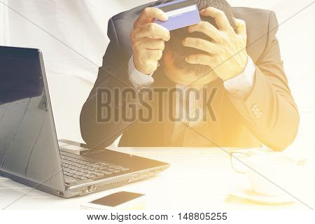 Young  business man   with credit card   accounting costs, charges, taxes and mortgage for paying bills looking worried and stressed