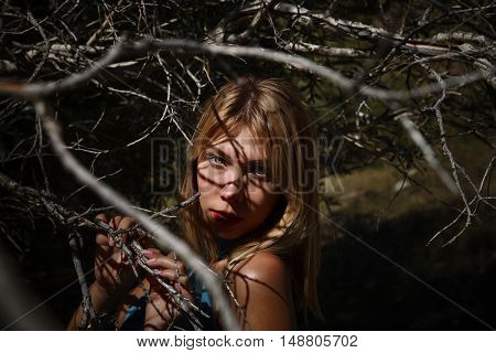 Fashion portrait of woman between trees branches