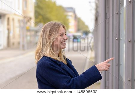 Smiling Young Woman Pointing To A Bus Time Table