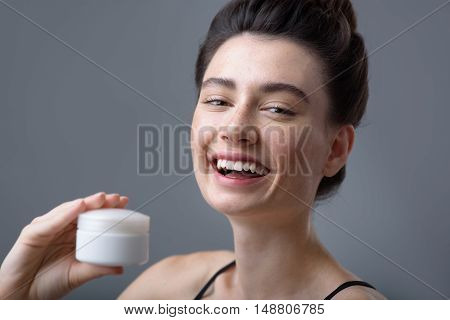 skin care concept, face of a freckled beautiful girl holding cream jar