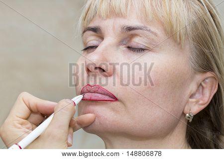 Lip tattoo woman in a beauty salon process