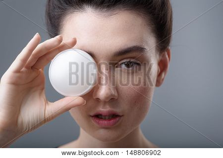 skin care concept, face of a young pretty woman holding cream jar