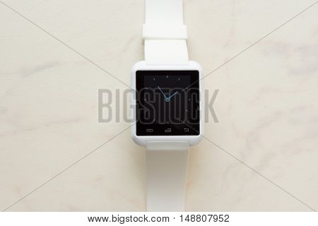 White Smart-phone And White Smart-watch. on wood desk.