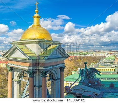 The golden domed bell tower of St Isaac's Cathedral with its bronze sculptures and St Petersburg skyline on the background Russia.
