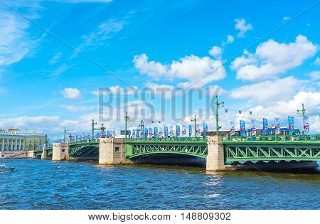 SAINT PETERSBURG RUSSIA - APRIL 25 2015: The view from Admiralty embankment of Neva river on the Palace Bridge one of the most famous sites in city on April 25 in Saint Petersburg.