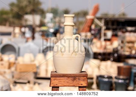 Traditional pottery kept on top of a wooden stool in Bahrain