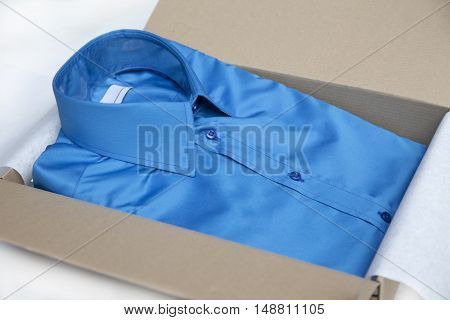 Blue shirt packed in paper gift box.