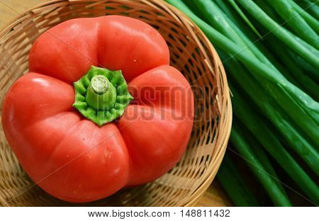 red paprika in basket with spring onions