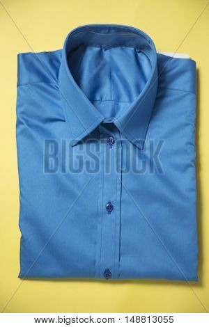 Blue shirt packed on the yellow background.
