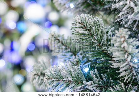 A branch of an artificial Christmas tree strewn with artificial rime