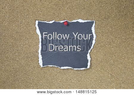 The phrase follow your dreams in text on a sticky note posted to a cork notice board.
