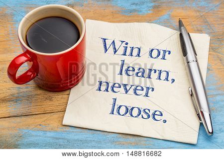 Win or learn, never loose - handwriting on a napkin with a cup of espresso coffee