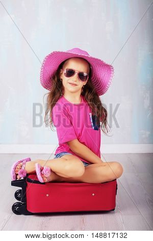 child with long hair in pink sitting on a suitcase. The concept of travel and lifestyle.