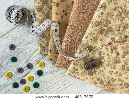 vintage cloth measuring tape thimble colorful buttons pins lie on a light wooden table. Top view