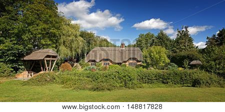 A panorama of a picturesque thatched cottage in the countryside. Image taken from public street.