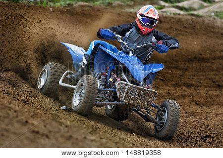 Quadbike ATV rider in the action on dirt road