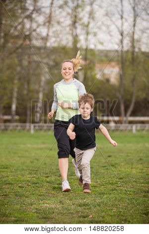 Happy son and mother doing exercises in the summer park. on the stadium outdoor. Sport activities with children. Healthy lifestyle. Fitness exercises. Young mother and son running together