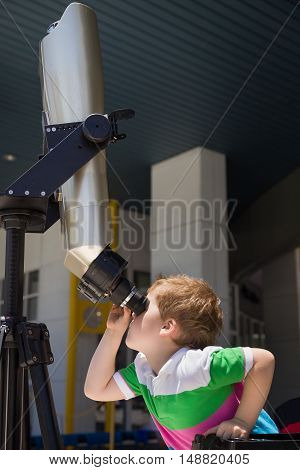 Cute smiling boy looking skyward through astronomical telescope. Child looking through tourist telescope exploring landscape.