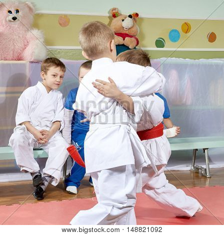 Children look sparring athletes in judo on the mats