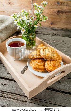 Cozy breakfast in spring or early autumn tea, freshly baked scones and bouquet of field's daisy and fascinating book. In wooden tray, Copy space