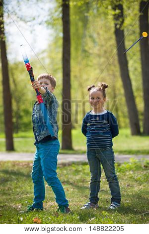 Cute kid boy archer with bow shooting in sunny summer day. little children shoot bow in the park. Outdoors. Sport activities with children. Sport and lifestyle concept. Aiming high