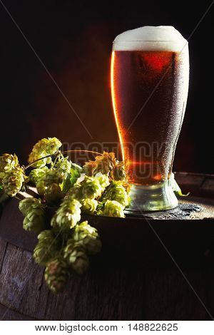 Pint of beer in a glass on a wooden barrel with hops