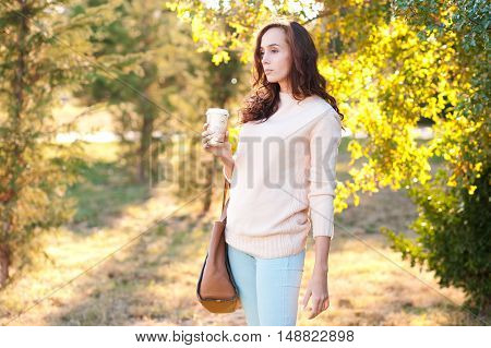 Young girl 20-25 year old wearing casual sweater and denim jeans holding cup of coffee outdoors. Posing over green nature background. .