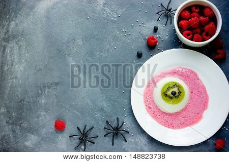 One eye panna cotta with kiwi and raspberry sauce Halloween recipe. Creative idea for kids dessert on holiday party top view empty space for text