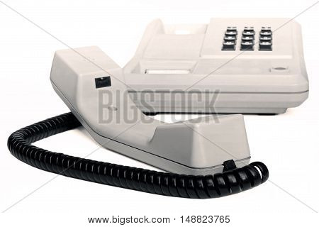 Old simple office desk phone in sepia isolated on white background